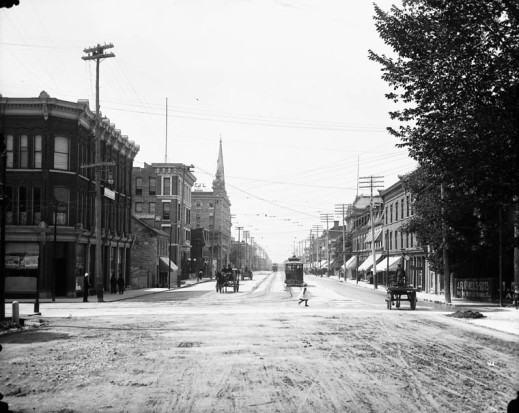 A black-and-white photograph showing a streetscape at a crossroads.