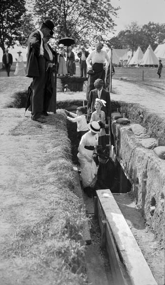 A black-and-white photograph of well-dressed men, women and children looking at and exploring an outdoor exhibit of a reconstructed Canadian military trench.