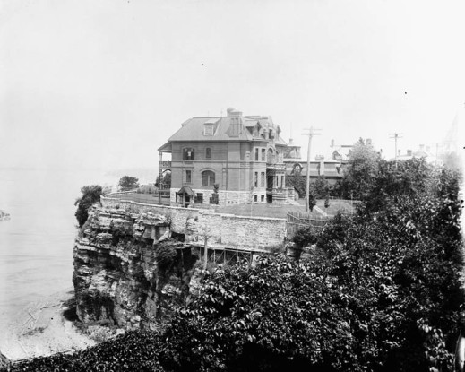 A black-and-white photograph of a large brick house perched on a cliff.