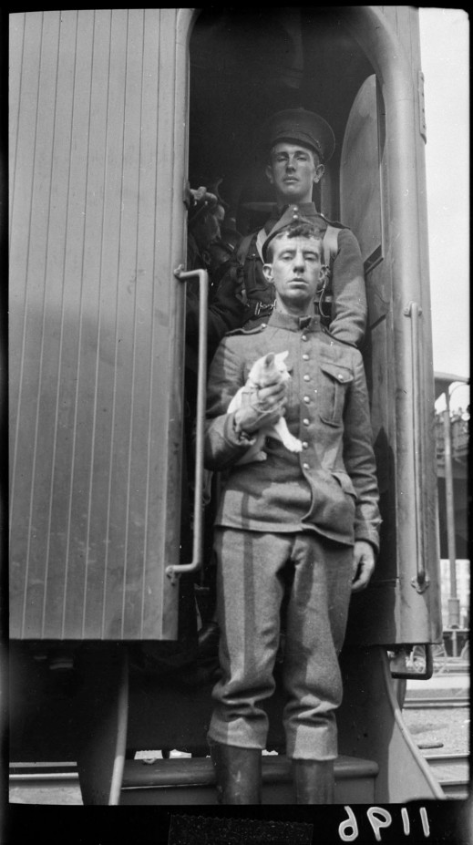 A black-and-white photograph of two soldiers descending the steps of a train car. They are both looking down at the photographer and one is holding a kitten.