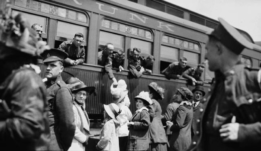 A black-and-white photograph of women, soldiers and children gathered outside a train. Other soldiers on the train are leaning out of the windows, presumably saying goodbye to their families.