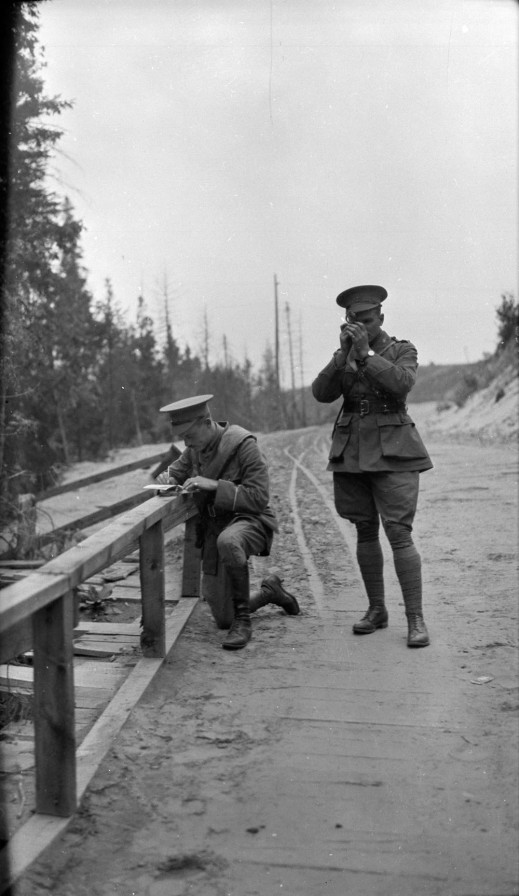 A black-and-white photograph of two soldiers stopped on a dirt road. One is taking a compass reading as the other takes notes.