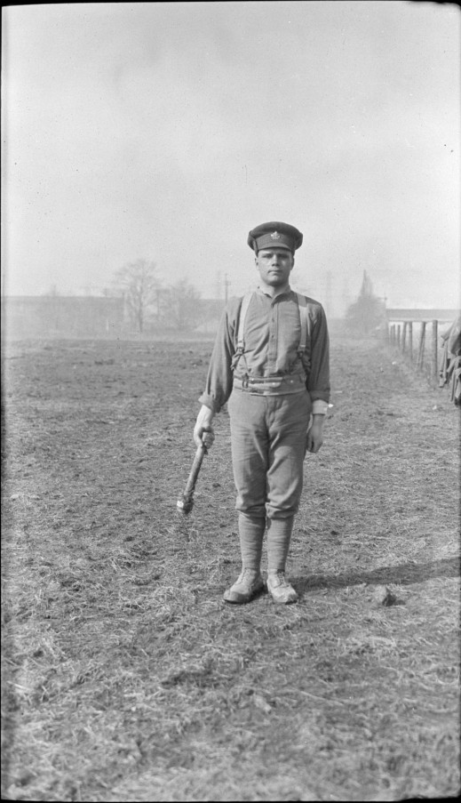 A black-and-white photograph of a soldier standing in a field holding a large wrench.