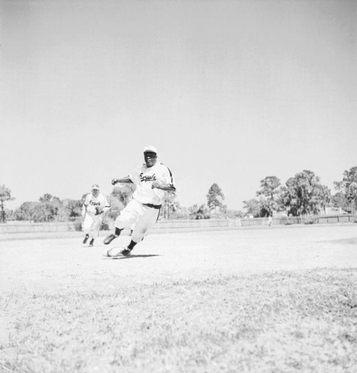 Black-and-white photograph of a baseball player running the bases. His foot is on third base and he is turning and heading to home plate. In the background are other players, and in the distance the outfield fence and trees.