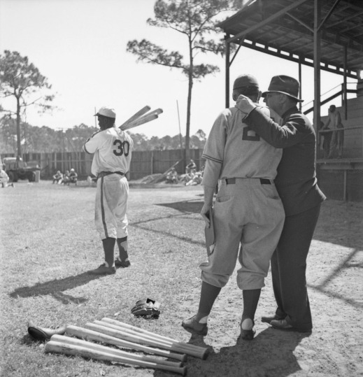 A black-and-white photograph of three men on a baseball field. Two men, one in uniform, the other in street clothes, stand in the foreground talking to each other. On the ground at their feet are two baseball gloves and a number of baseball bats. In the background, another player, in uniform, holds three baseball bats on his right shoulder. In the distance, people stand or sit on the ground and in the bleachers.