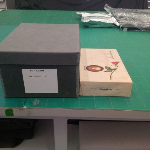 A colour photograph showing, on the right, the Laura Secord chocolate box that the material was original received in, and to the left, the new container the Dictaphone belts are stored in for the long-term preservation of this collection.
