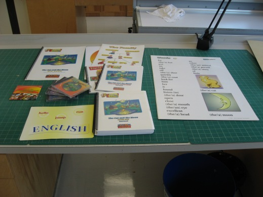 A colour photograph showing a multimedia kit containing a variety of items spread across a worktable.