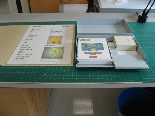 A colour photograph of a custom container and a custom folder for a poster.