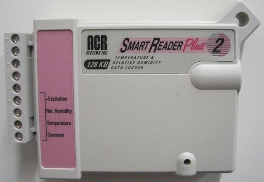 Photographie en couleur d'un boîtier, à peu près de la taille d'une audiocassette, fixé sur un mur. L'appareil enregistre deux différents types de données : l'humidité relative et la température à l'intérieur, ainsi qu'à l'extérieur, grâce à des connexions pouvant être reliées à des sondes de température et d'humidité.