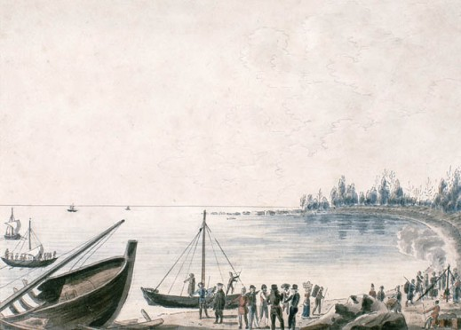 A watercolour on wove paper showing the bow of a wrecked boat onshore in the immediate foreground at the left. Several people are standing on the beach, working or conversing.