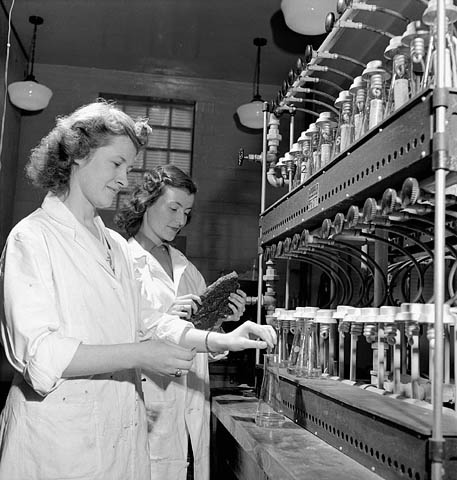 Black and white photograph showing two female laboratory technicians dressed in white lab coats. The one in the foreground is stirring a solution in a test tube, while the one in the background is holding a piece of synthetic rubber in her hands and looking at it.