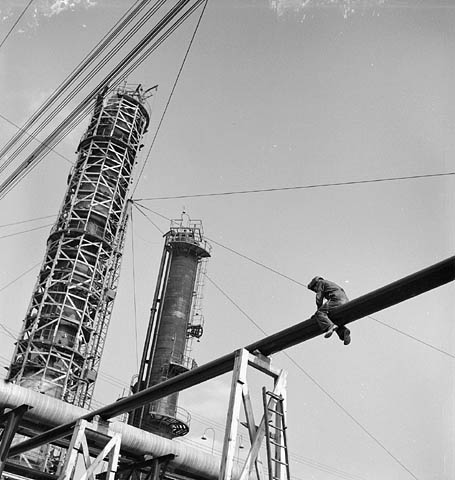 Black and white photograph taken from the ground showing, in the foreground, a welder straddling a pipe suspended in the air and, in the background, two extraction chimneys, one of which is still covered in scaffolding.