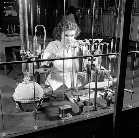 Black and white photograph showing a female laboratory technician dressed in a white lab coat, doing experiments while facing laboratory equipment. In the background, we see the back of another female laboratory technician as well as other equipment.