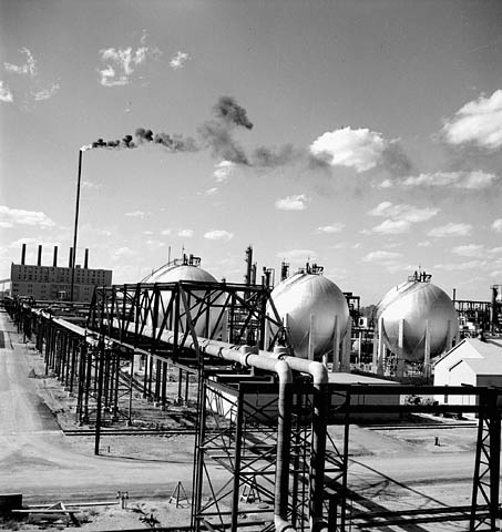 Black and white photograph showing three large spherical reservoirs and a complex network of pipes in the foreground. In the background we see a tall chimney spewing out flames and smoke as well as a building with five other chimneys.