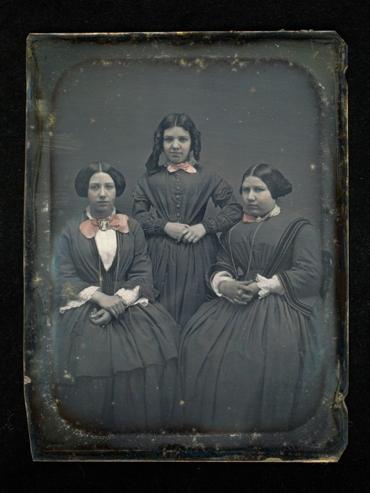 A hand-tinted daguerreotype of three young women. The woman in the middle is standing between two women, who are seated.