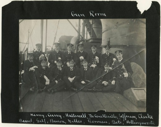 "A black-and-white photograph showing a group of men sitting or standing on the deck of a ship. The photo is mounted on a black background with the words ""Gun Room"" written at the top and a list of names at the bottom."