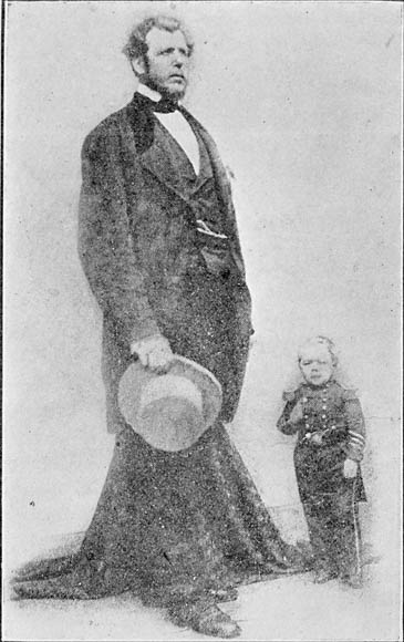 A black-and-white photograph of two men standing: one is very tall and the other is very short.