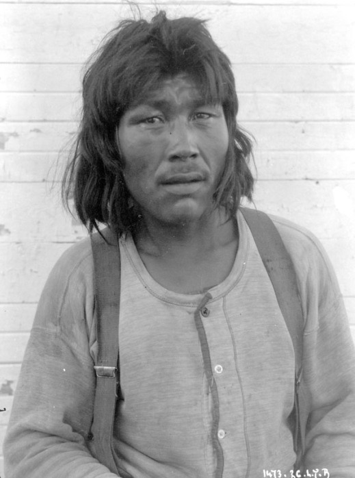 A black-and-white photograph of an Inuit man wearing a shirt and suspenders and looking directly at the photographer.
