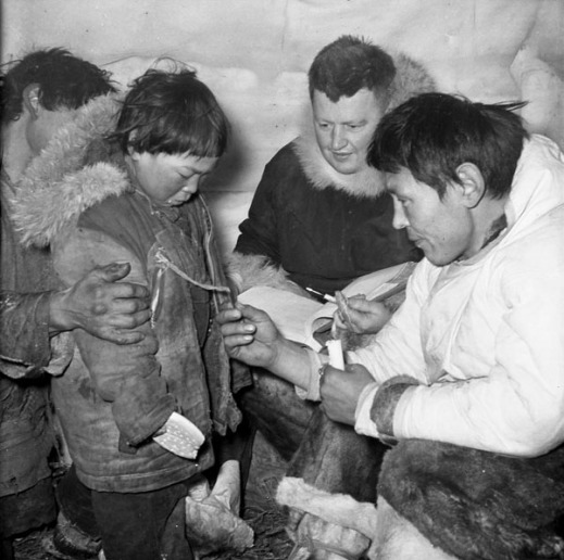 A black-and-white photograph taken inside an igloo of two men reading a disc number attached to a boy's parka.