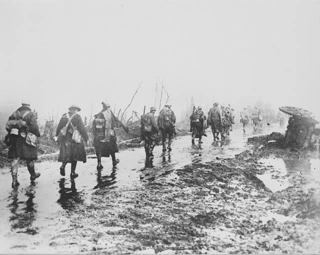 Photographie en noir et blanc de soldats qui marchent sur un étroit sentier boueux, s'éloignant du photographe.