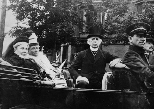 A black-and-white photograph showing a group of peopleA black-and-white photograph showing a group of people sitting in a car. sitting in a car.