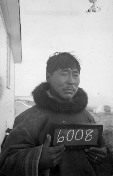 A black-and-white photograph of an Inuit man holding a small chalkboard with the number 6008.