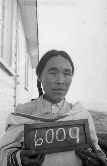 A black-and-white photograph of an Inuit woman holding a small chalkboard with the number 6009.