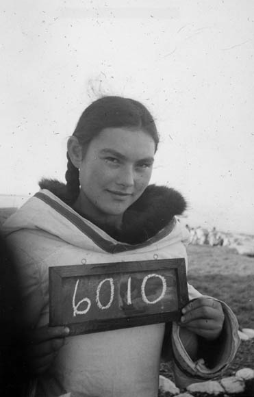A black-and-white photograph of an Inuit woman holding a small chalkboard with the number 6010.