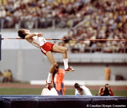 Colour photograph of a man competing in the high jump event. The photo depicts him in the air approaching the bar. Behind the mat are photographers. The crowd is seated in the background.