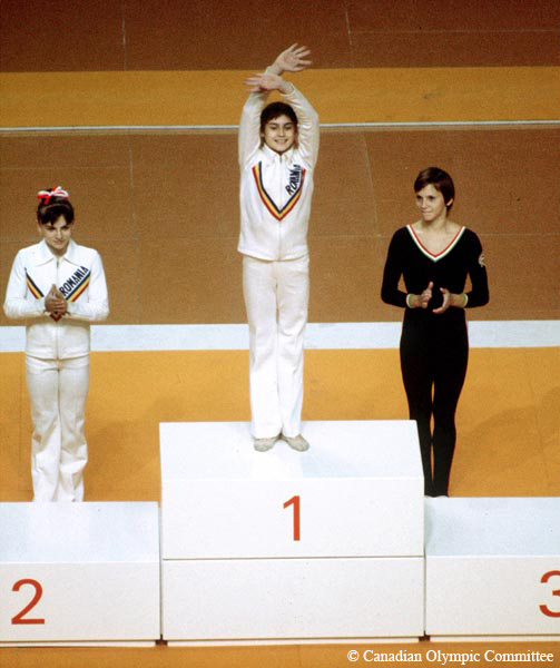 "A colour photograph depicts a young woman standing on the podium waving to the crowd. She is wearing a white track suit with ""Romania"" written on it. Behind her on the floor are two other young women."