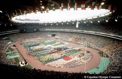 A colour photograph depicts the inside of Olympic Stadium, Montréal. The athletes of the competing nations assemble on the infield of the stadium. The flags of the competing nations hang from the rafters.