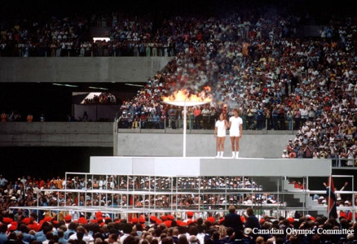 A colour photograph depicts two young people standing on a raised platform in a crowded stadium. They each have a hand on a torch which they are holding aloft. Beside them is a large ceremonial cauldron that is lit with a flame.