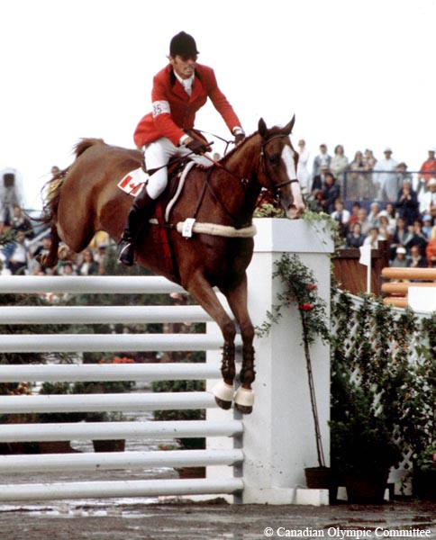 Colour photograph of a man riding a horse as they complete a jump over a fence in the equestrian competition. The audience is seated in the background.