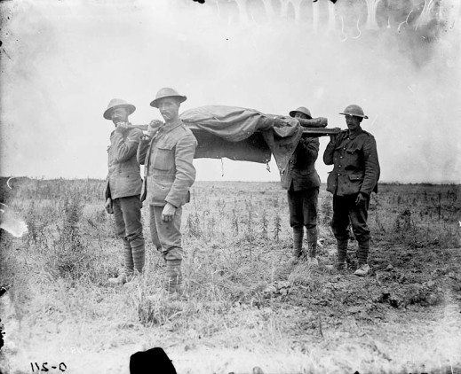 A black-and-white photograph of four soldiers carrying a stretcher with a shrouded body on it through a devastated landscape.