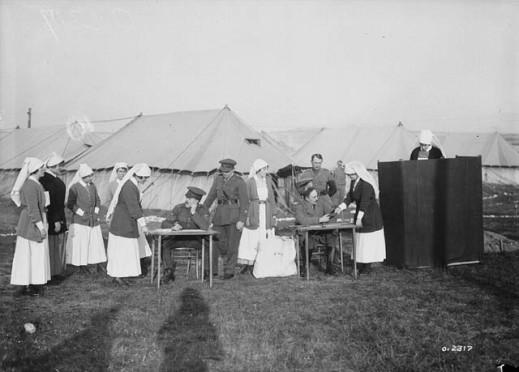 A black-and-white photograph showing a group of nursing sisters waiting in line to cast their votes at an outdoor polling station. Four male officers oversee the proceedings while one sister casts her vote behind a screen. In the background are encampment tents.