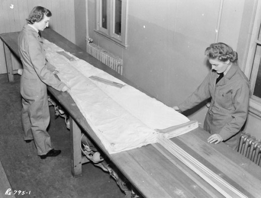A black and white photo showing two women dressed in coveralls standing on either side of a long table, upon which a folded parachute rests.