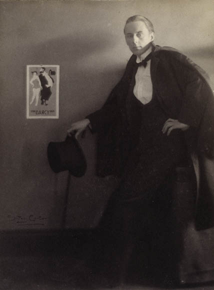 A black-and-white photo of a man in an evening suit standing beside a poster on the wall.