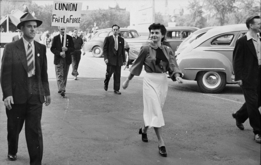 "A black-and-white photograph showing a woman walking down a street; behind, there is a man with a sign that says ""L'union fait la force"" [Unity makes strength]"