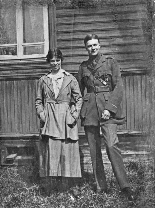 A black-and-white photograph showing a couple standing in front of a wooden building. She may be in a nurse's uniform and he is wearing a Russian military uniform.