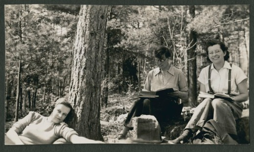 A black-and-white photograph showing three women outdoors under a tree. The woman on the right is seated and smiling at the photographer, the one in the middle is also seated but engrossed in her book, and the one on the left is lying down and looking at the photographer.