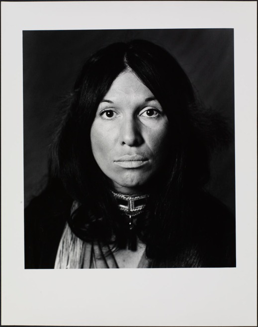 A black-and-white photo portrait of a woman with long dark hair looking directly at the photographer.