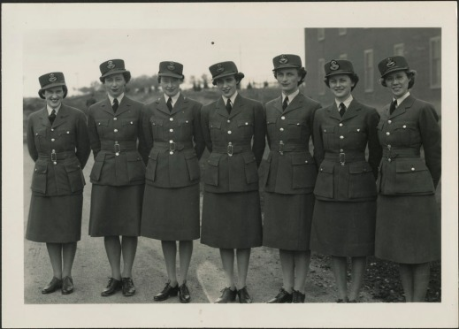 A black and white photo showing seven members of the Royal Canadian Air Force Women's Division. The women stand outdoors, their hands clasped behind their backs as they smile at the camera. The figures wear standard issue uniforms including jackets, skirts, caps and shoes.