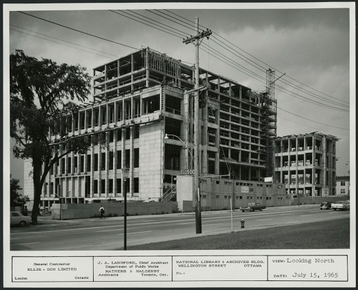 A black-and-white photograph showing the unfinished facade of a 10-storey building. There is construction board on the ground floor. There are cars (including a VW bug!) and pedestrians going about their business.