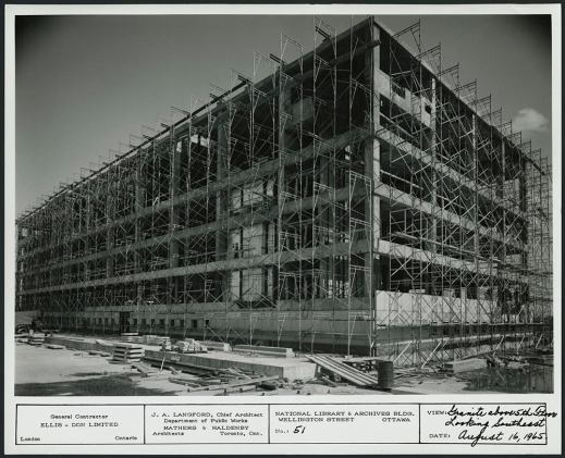 A black-and-white photograph showing a building completely surrounded by scaffolding.