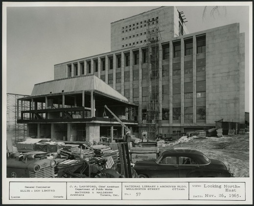 A black-and-white photograph showing a construction site with a partially finished building.