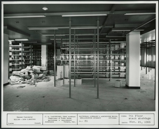 A black-and-white photograph a low-ceilinged room with rows upon rows of shelving in various states of completion.