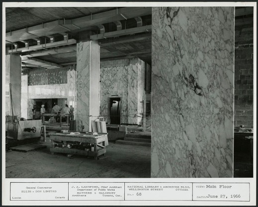 A black-and-white photograph showing a partially completed interior covered in deeply-veined, white Carrera marble.