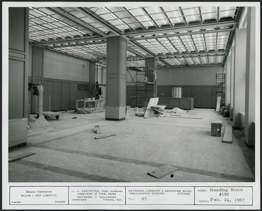 A black-and-white photograph of a large room with scaffolding and construction materials scattered about.