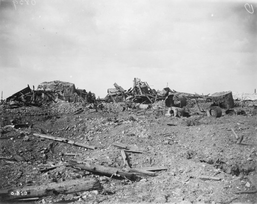 A black-and-white photograph of a ruined industrial building in a destroyed landscape.