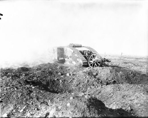 A black-and-white photograph of a British heavy tank advancing through a shell-cratered landscape.